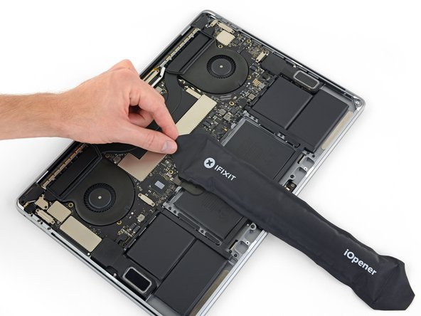 Apply mild heat to the trackpad ribbon cable to soften the adhesive securing it to the battery.