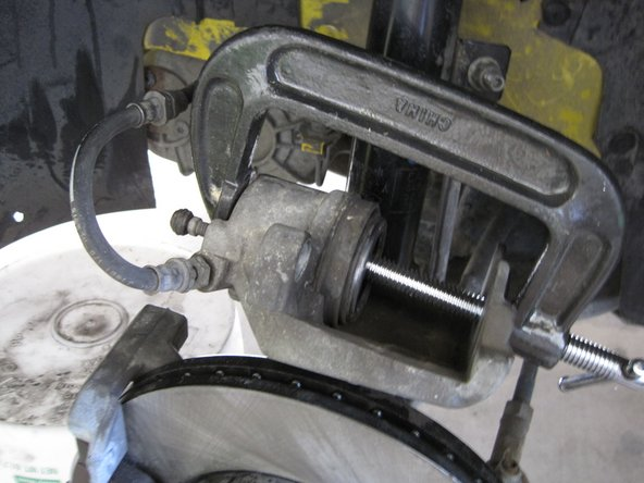 Compress the caliper piston with a C-clamp.