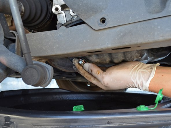 Loosen the drain plug by hand until it comes off completely and oil begins to drain out of the oil pan.