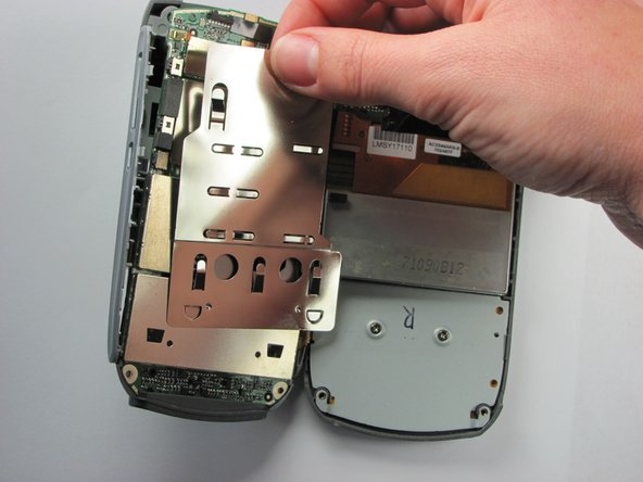 Slide the slim metal plate upwards until it disconnects from the motherboard.