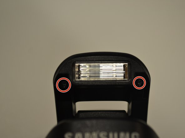 Once the flash head is up, unscrew the two black 4mm Phillips head screws located on either side of the flash bulb.