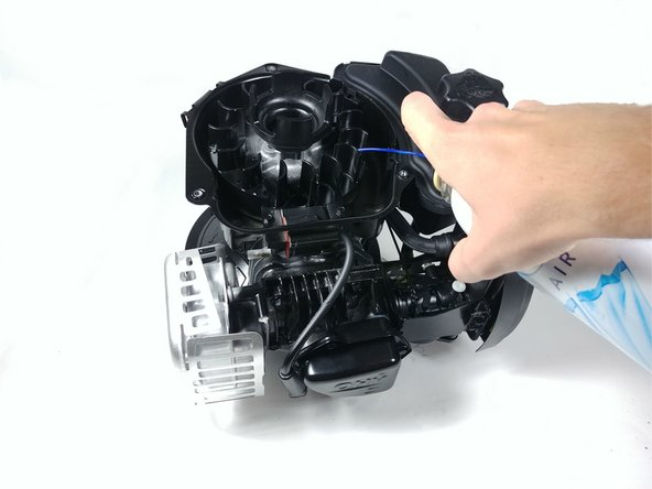 Using compressed air or a rag, clean debris from the flywheel.