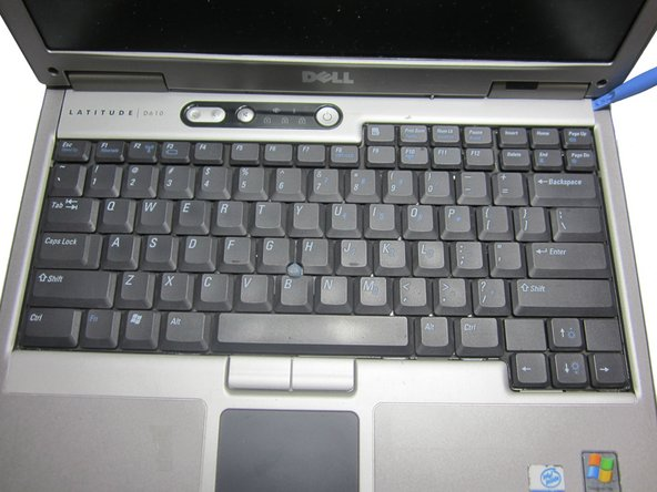 Use an opening tool or flat tool to remove the plastic cover above the keyboard.