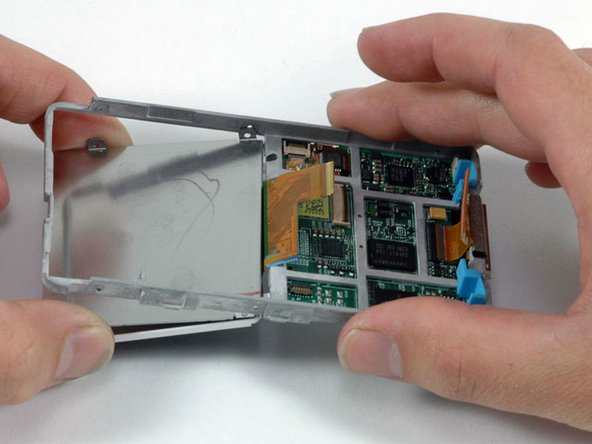 Lift the framework assembly up, and slide the display and LCD metal backplate out of the framework assembly.
