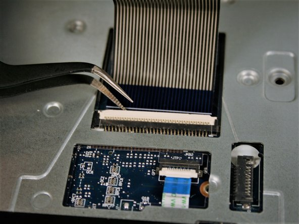 Using tweezers, lift up clip to remove keyboard ribbon cable.