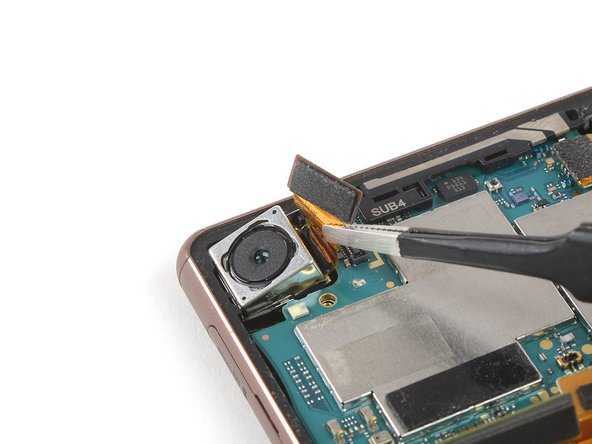 Use a pair of tweezers to lift the rear camera out of its recess and remove it.