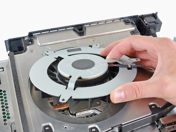 Remove the fan from the heat sink, minding its cables that may get caught.