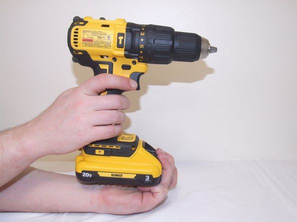 Grab the drill in one hand and cup the battery (located at the bottom of the drill) with the other hand.