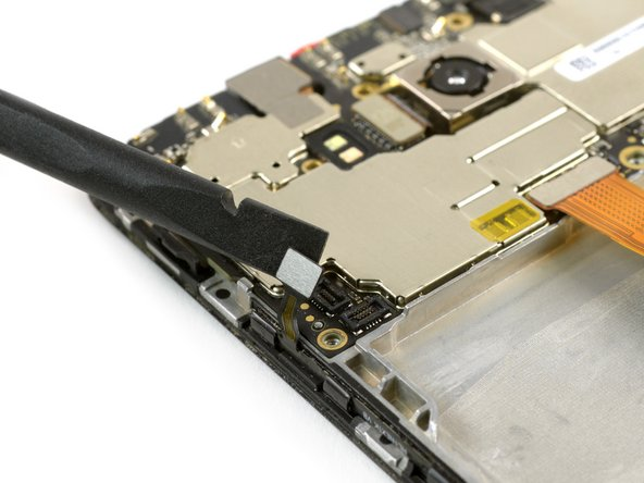 Use the flat end of a spudger to disconnect the volume and power flex cable on the bottom left side of the mainboard.