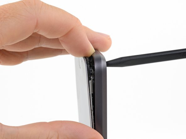 Use a finger to maintain separation between the display assembly and the rear case while you remove the spudger.