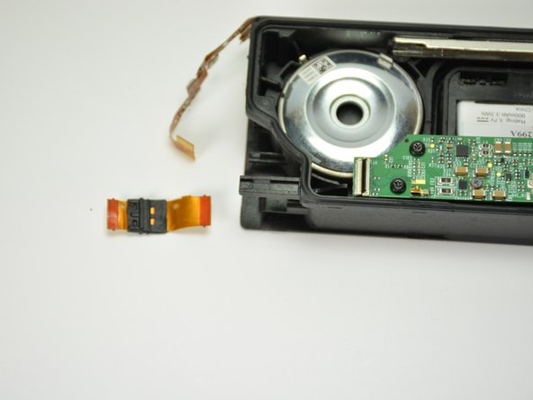 Very carefully pull the motherboard connection ribbon through the plastic casing, removing it from the plastic casing.