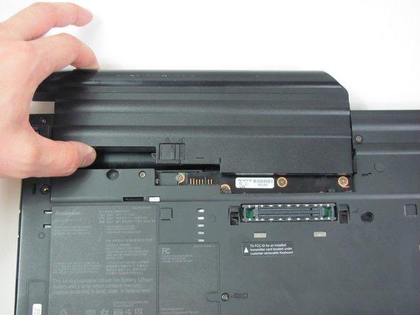 Une fois que l'onglet est sur la position déverrouillage (à droite), tirez la batterie vers l'extérieur pour la retirer du ThinkPad.