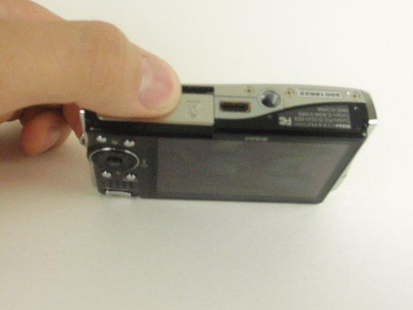 Slide the battery door in the direction of the arrow, toward the LCD screen. The door will then swing open.