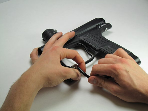 Firmly grasp hold of the ring on the bottom of the 90 degree silver fitting on the front of the gun.