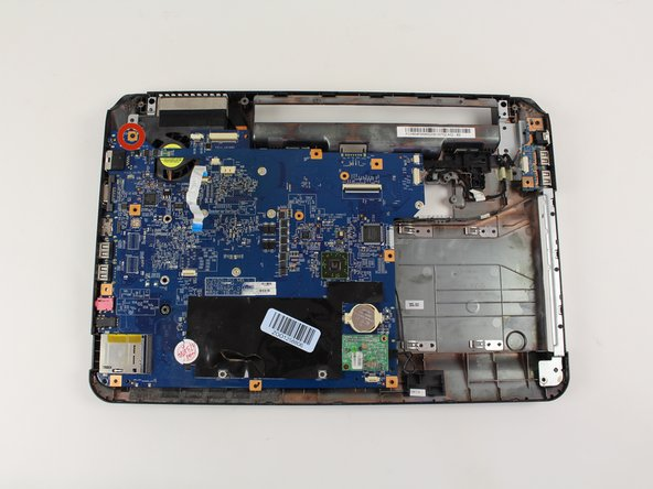 """Remove the 3/16"""" screw securing the motherboard with a Phillips #0 screwdriver."""