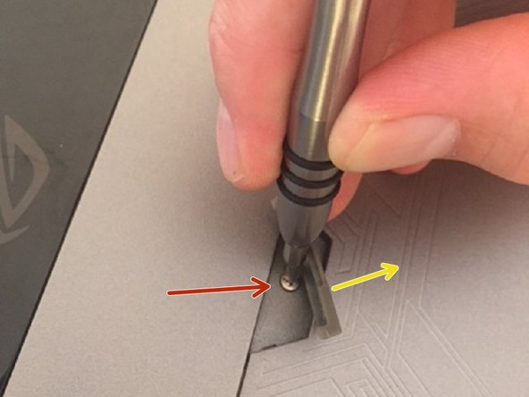Lift up rubber tab and unscrew screw, it will stay attached to cover.