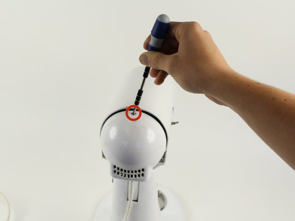 Using a Phillips #2 screwdriver, remove the 10 mm screw from top of back cover.