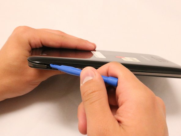 With the blue plastic opening tool, use the lock screen switch by the volume button as an access point to gently lift the back cover off.
