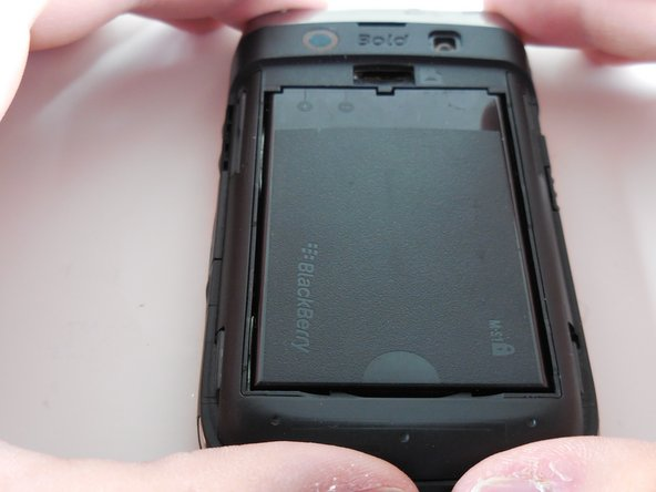 Remove the battery by prying the bottom of the battery upward.