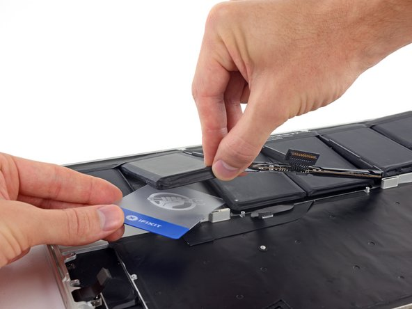 While lifting the plastic frame out of the way, push one corner of your plastic card underneath the outside edge of the first center battery cell.
