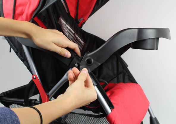 """Unsnap the """"Child Tray"""" by pulling outwards on the plastic connectors on either side of the stroller.  As you pull, lift upwards to completely remove the tray from its connection to the stroller's frame."""