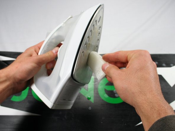 Hold the iron perpendicular to the snowboard and rub the wax directly onto the iron.