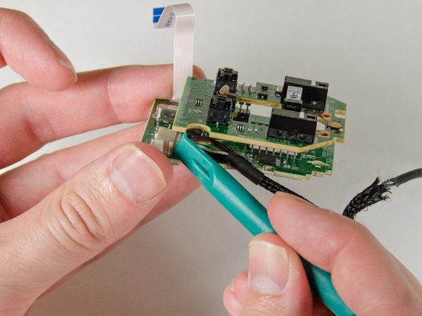 Carefully pry on each side of the mouse connector until the cable comes free.
