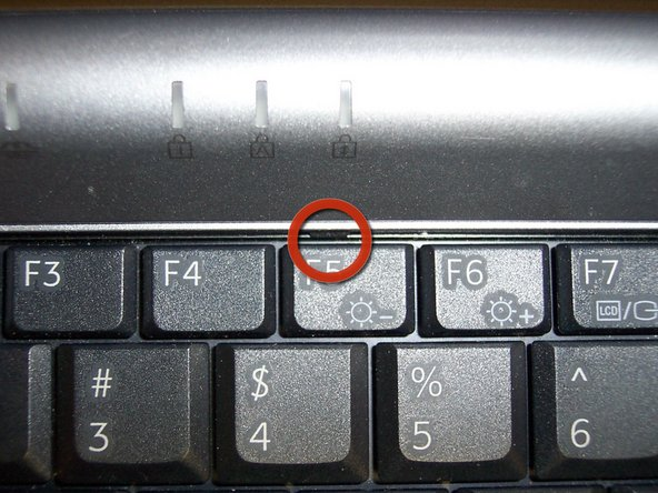 Loosen 2 latches holding the keyboard down with the flat tip screwdriver, one by the F5 key, and the other by the Num Lock key. Move keyboard towards the touch pad and pull up.