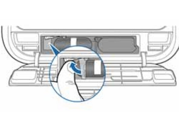 Locate the metal lock clip above the battery on the left-hand side.