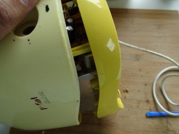 Setze ein Kunstoffwerkzeug in die Naht zwischen Ober- und Unterteil ein und vergrößere ringsum den Spalt.