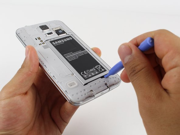Lift the battery upward with your finger or plastic opening tool by pushing on the notch located on the bottom of the battery.