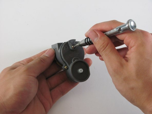 Next, with the same head remove the screw holding the plastic housing together