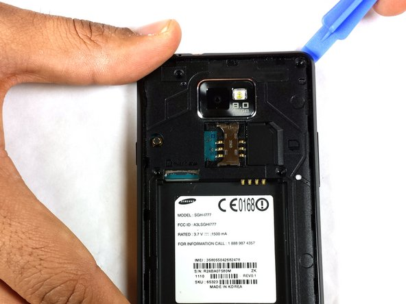 Move along the outside edge with the plastic tool, popping the connections to the phone.