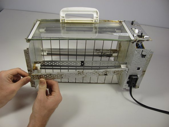 Remove the the heating coil protection bar from the toaster unit by first pulling out the left side.