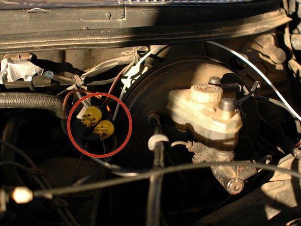 Hebe als Erstes die Haube hoch und schaue auf der Fahrerseite in die Nähe des großen runden Bremskraftverstärkers. Du findest dort das gelbe Rückschlagventil, an dem zwei Anschlüsse sind. Ein Anschluss ist ein Y - Verbinder, aus dem zwei gelbe Leitungen herausgehen. Das ist die Versorgungsleitung für das Unterdruck-Zentralverriegelungsystem.