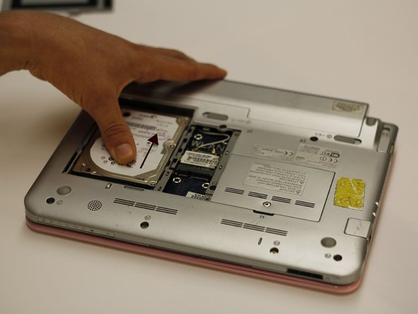 With the panel removed, slide the hard drive towards the top of the netbook with moderate force.