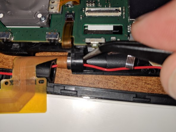 Finish sliding the ribbon cable through the hinge and free the red wifi wire, as well.