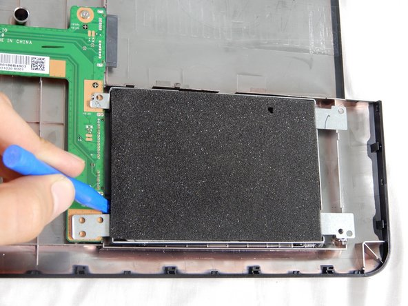 Using the blue plastic opening tool in the iFixit tool kit, slide the hard drive to the right to remove it from the case.