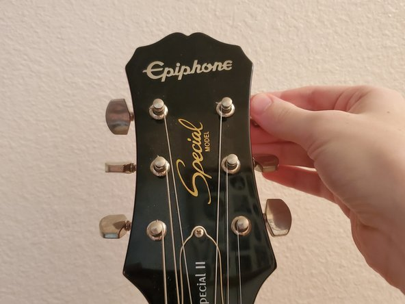 Loosen the strings by turning the tuning pegs. The direction will vary depending on the side of the peg.
