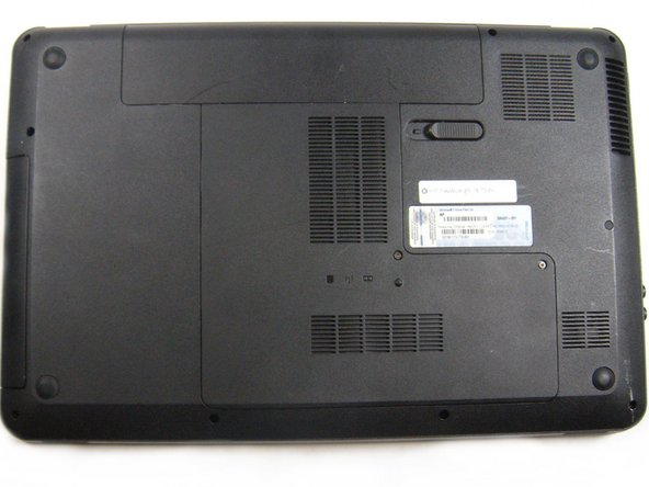 Flip the computer so the bottom is facing up with the battery away from you.