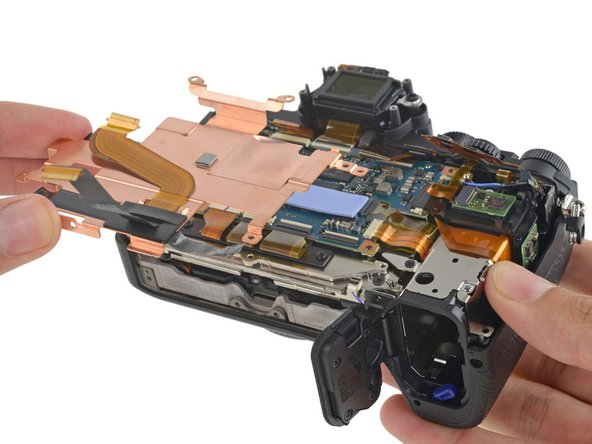 With the rear housing and button assembly removed, the motherboard shield comes out with very little resistance.