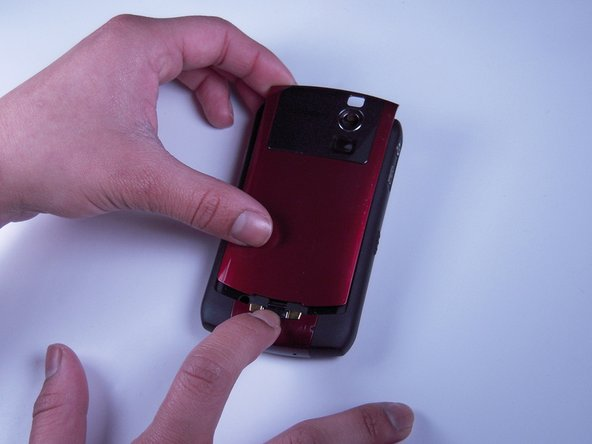 Press down on the battery release button and slide the back cover up with your thumb.