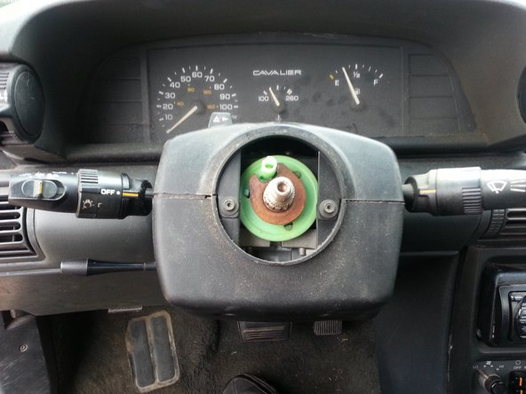 """Remove the steering shaft nut and pull off the steering hub. A steering wheel puller may be required. Use caution as the steering hub may pop loose. Next, remove the two """"torx head"""" screws behind the steering hub that hold the two plastic covers together."""