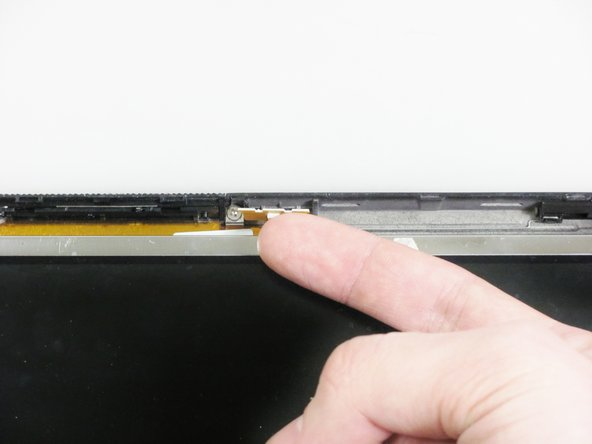 At the top of the screen, detach the small white clip by pulling it towards you with your finger.