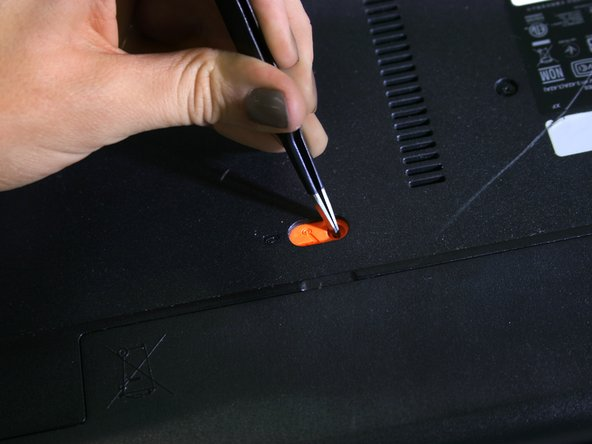 Using  a small tool such as tweezers or a pen,  slide the orange  switch completely to the left to unlock  the battery.