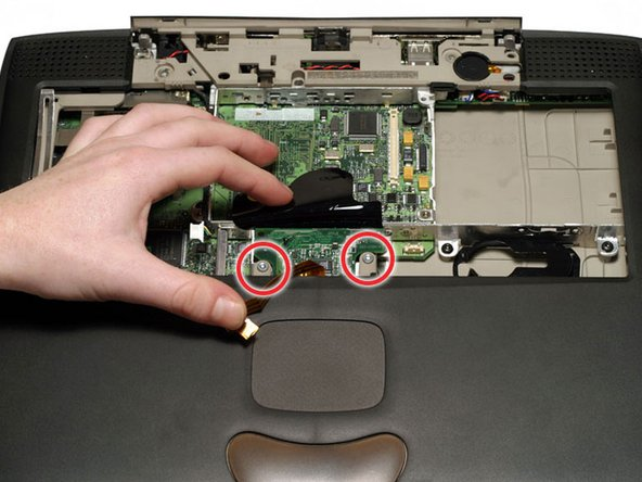 Turn the Lombard so that the trackpad is nearest you and slide the thin plastic shield away from you, out from under the black casing.