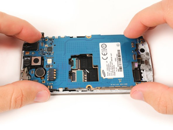 Gently lift the motherboard up and partially away from the device.