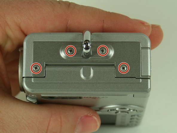 On the side of the camera, remove the four 4.75 mm screws that sit near the wrist strap mount.
