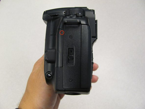 Remove the 4.8 mm black screw on the left side of the camera.