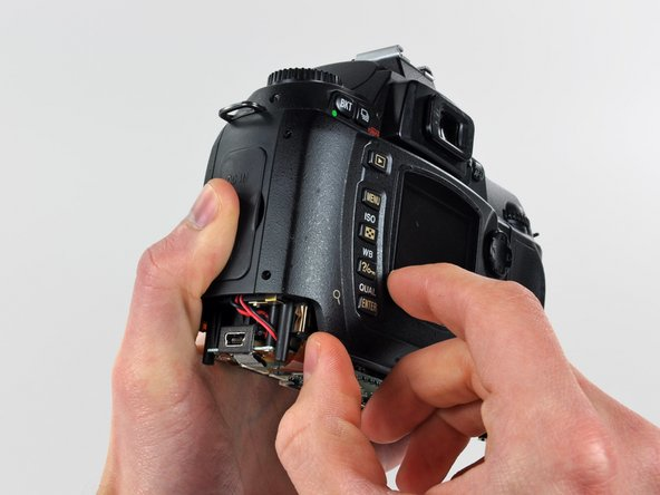 Carefully pull the sides of the rear cover away from the body of the D70.